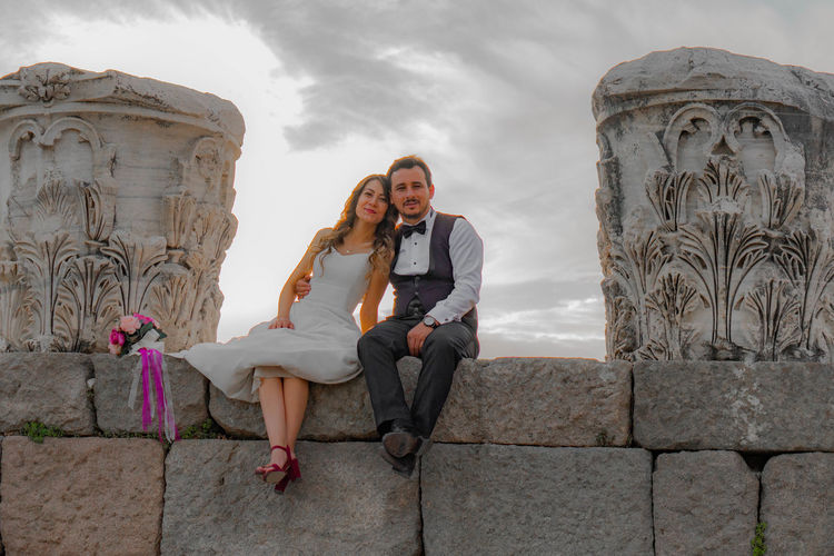 Portrait of smiling bride with groom sitting on stone wall at old ruin