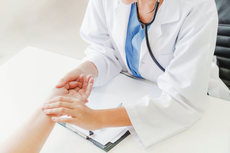 Midsection of doctor taking pulse of patient on table