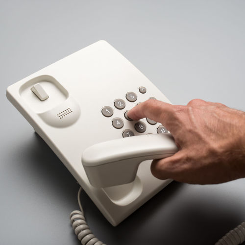 Close-up of hand holding camera over white background