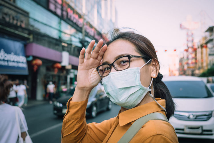 Portrait of woman wearing mask while standing on road