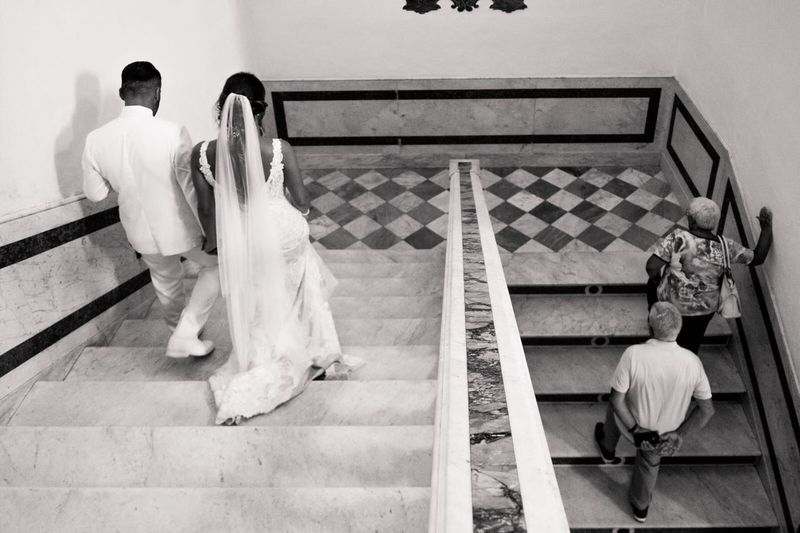 Rear view of couple walking on staircase