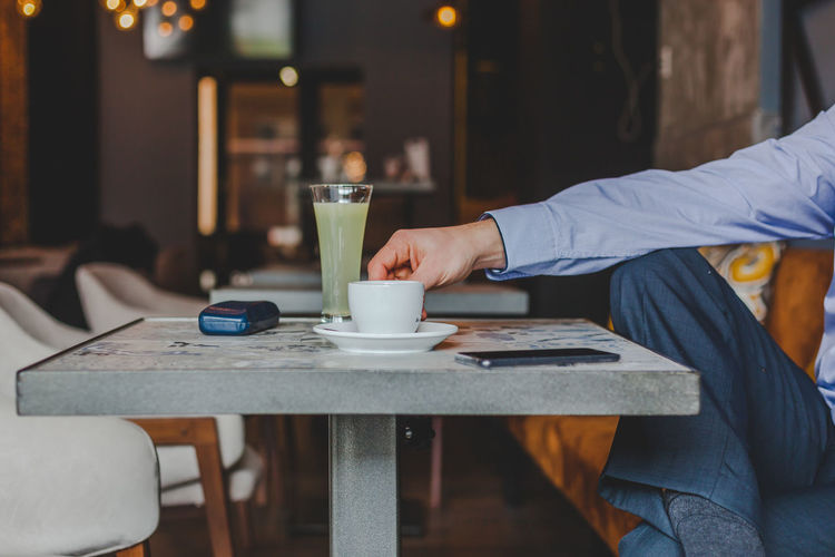 Midsection of businessman holding coffee cup on table in cafe