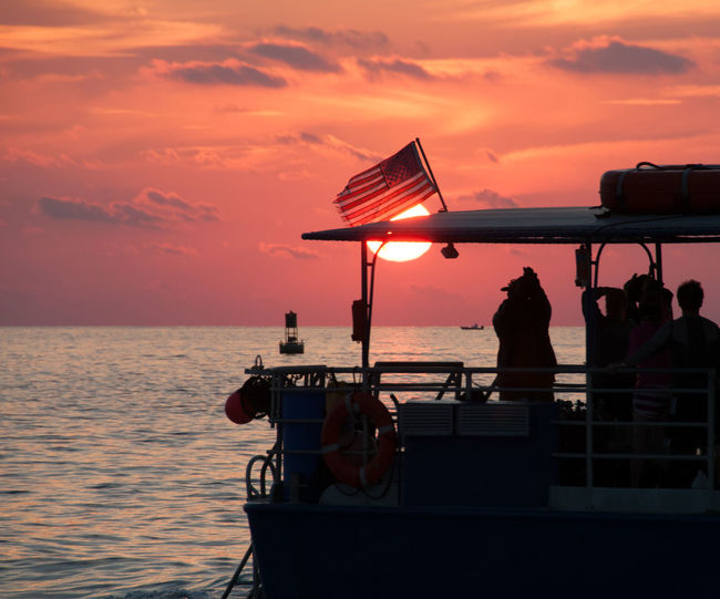 People on boat at sea photographing scenic sunset