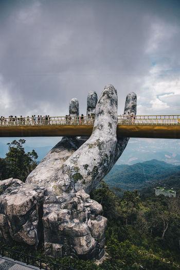 Bridge over rocks against sky