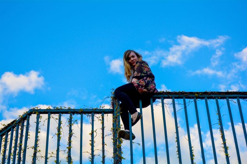 Low angle view of woman sitting on fence against blue sky
