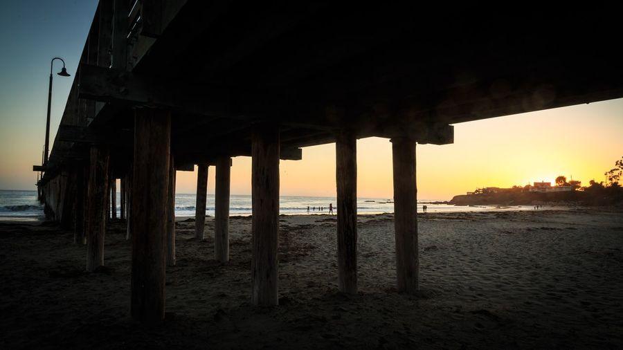 Silhouette of below bridge over sea against sky