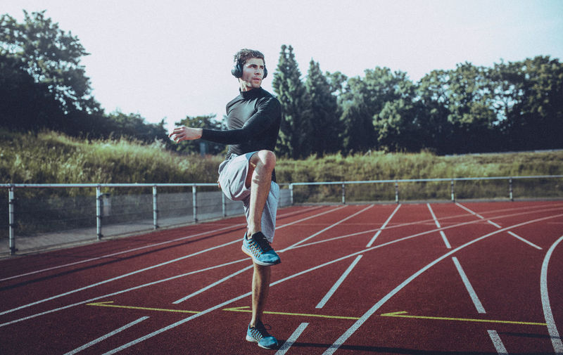 Young Man Exercising On Running Track
