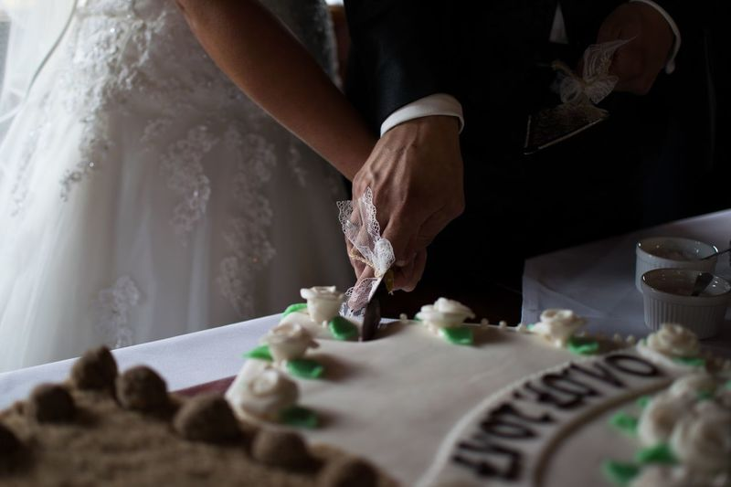 Close-up of young couple cutting wedding cake