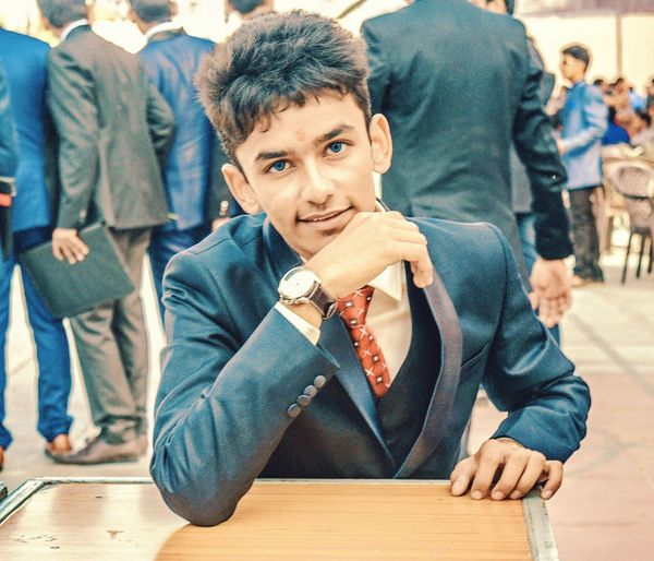 Portrait of teenage boy wearing suit sitting at table