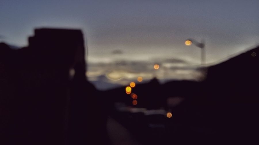 Defocused image of silhouette city against sky at sunset