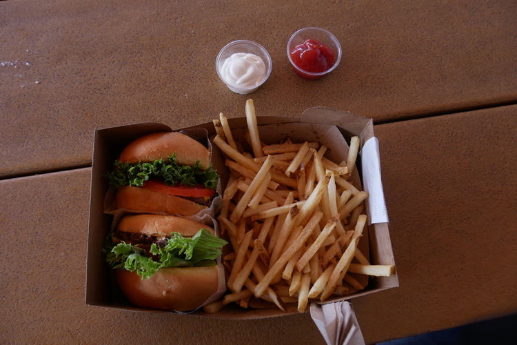 High Angle View Of Burgers With French Fries On Table
