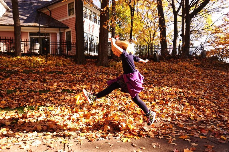 Full Length Autumn Tree One Person Leisure Activity Leaf Outdoors Real People Building Exterior Lifestyles Motion Nature Day Built Structure Happiness Sports Clothing Warm Clothing Beauty In Nature Architecture Human Body Part