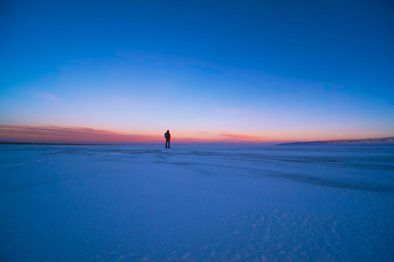 Man standing on snowy landscape against sky during sunset
