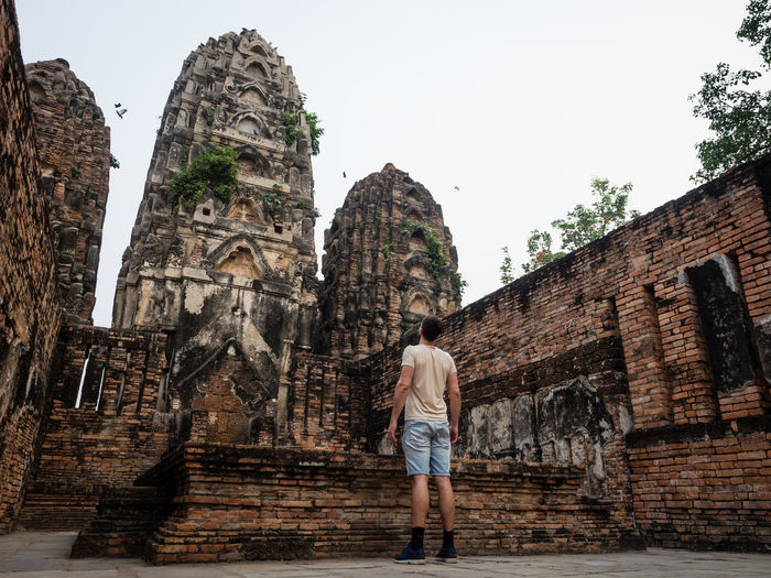 Low angle view of man standing against ancient temple