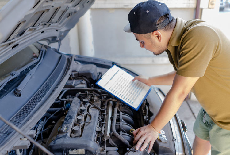 Side view of man holding checklist while looking at car engine