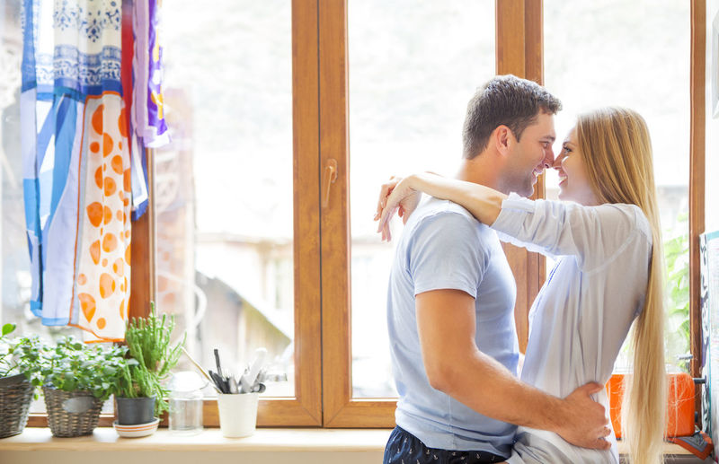 Young couple kissing against window
