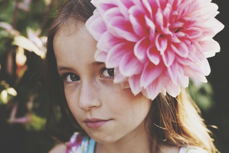 Close-up portrait of girl with pink flower