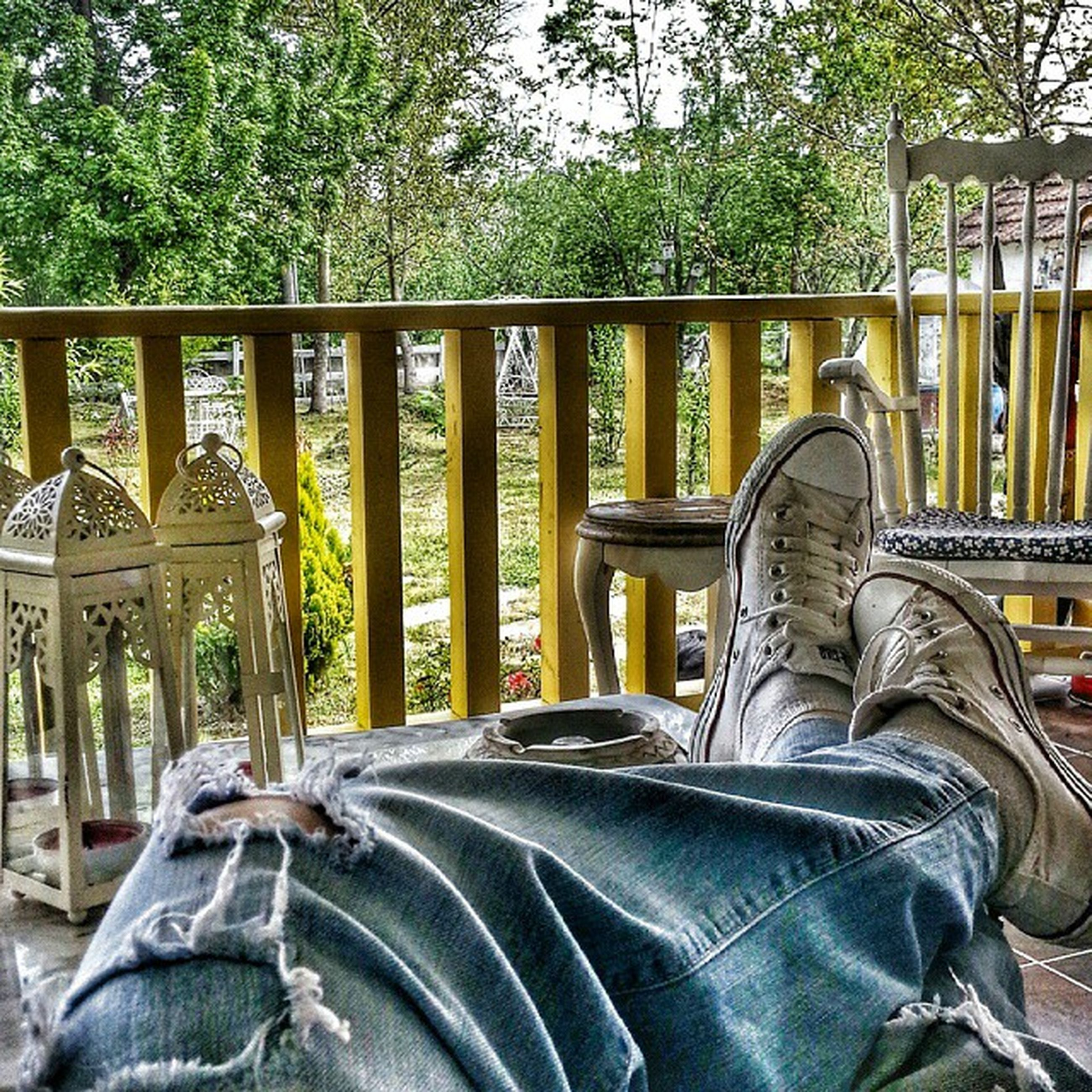 low section, person, shoe, sitting, relaxation, lifestyles, men, jeans, personal perspective, bench, leisure activity, wood - material, tree, casual clothing, footwear, chair, standing, day