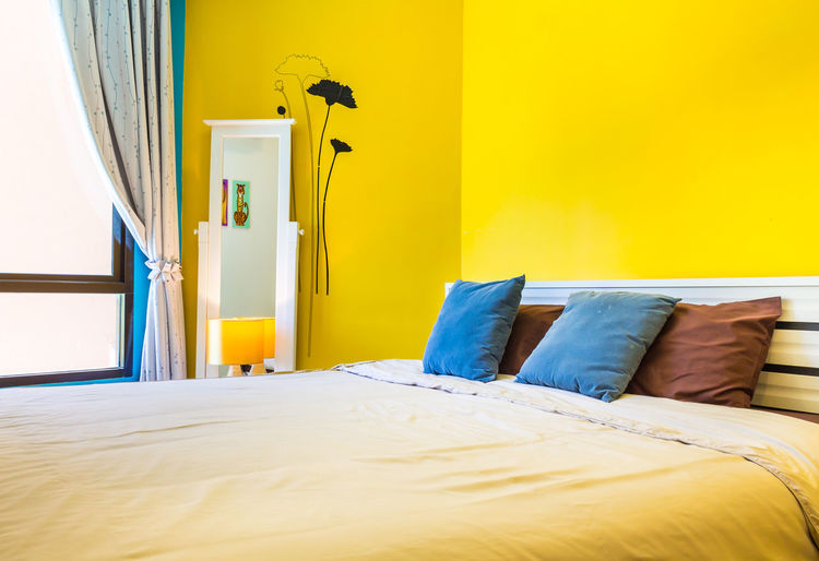 View of yellow bed in bedroom