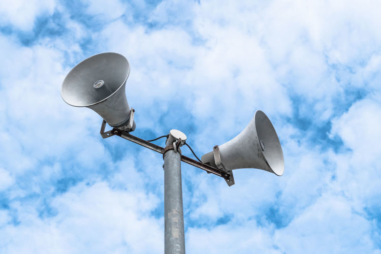 Low angle view of megaphones against cloudy sky