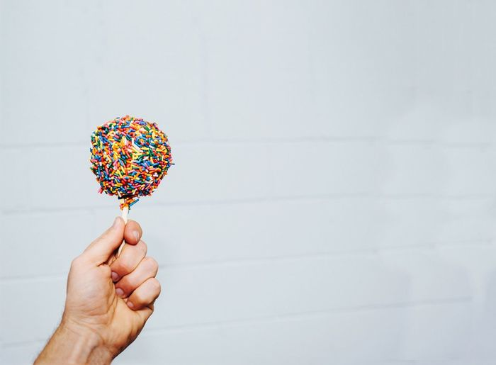Cropped hand of man holding sweet food by white wall