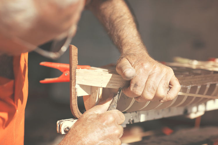Close-Up Of Man Working On Wooden Boat Model
