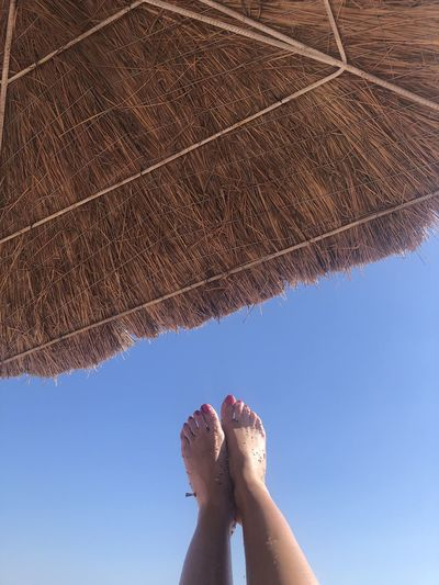 Low section of woman with feet up against clear sky