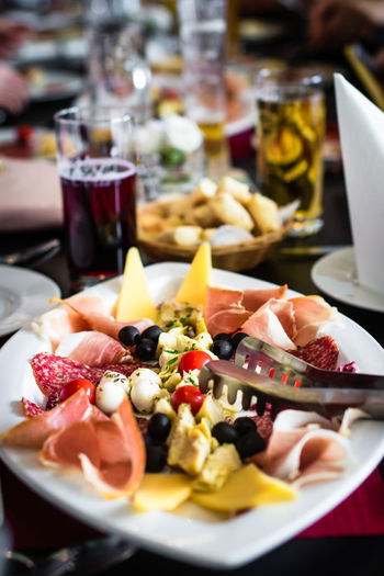 Close-Up Of Antipasto With Serving Tongs In Plate On Table At Restaurant
