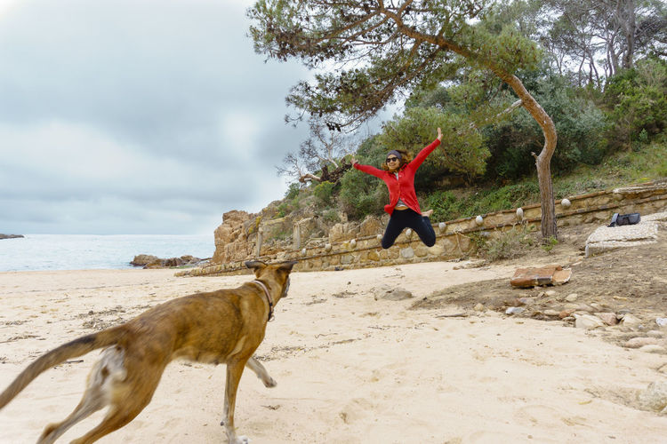 Full Length Of Woman With Dog Jumping At Beach