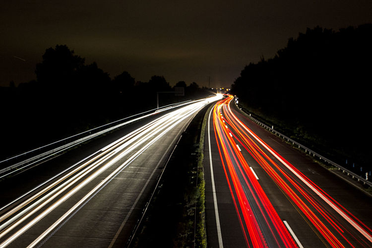 Light trails on roads against sky at night