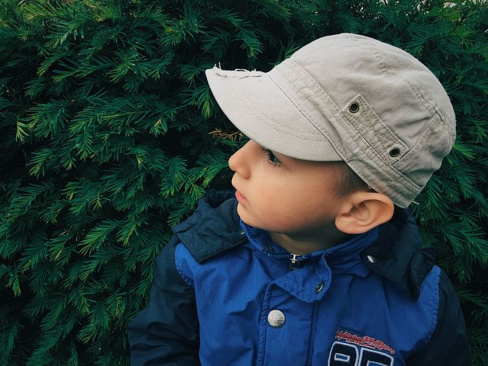 Cute Boy Wearing Cap While Looking Away In Park During Winter