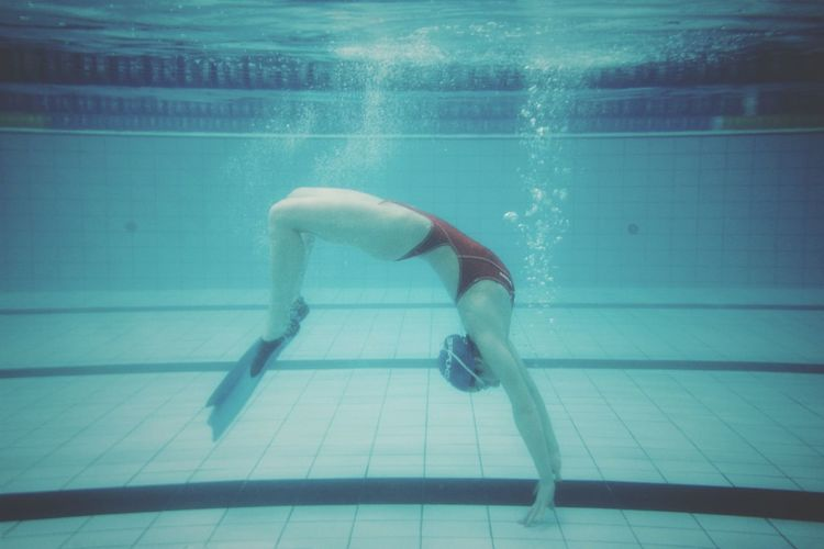 Side view of woman swimming underwater in pool