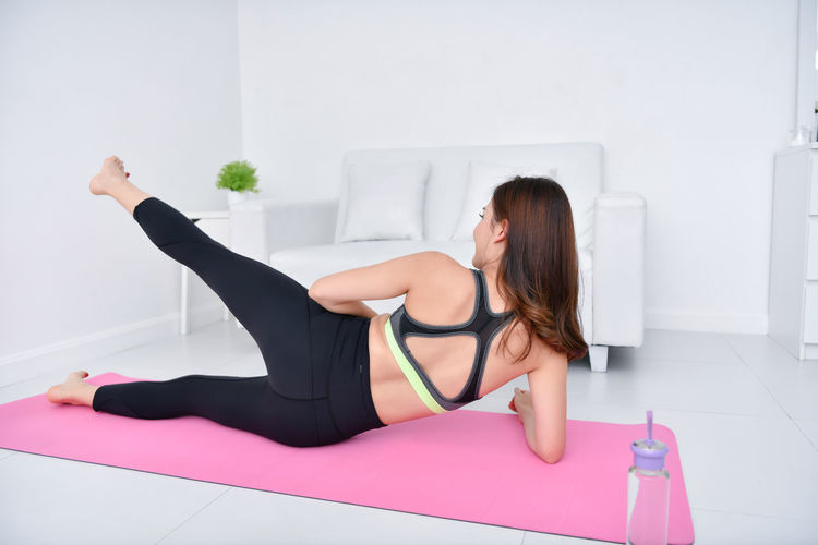 Full length of woman doing yoga while lying on mat at home