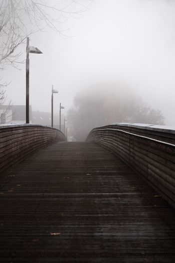 Empty footpath by railing against sky during winter