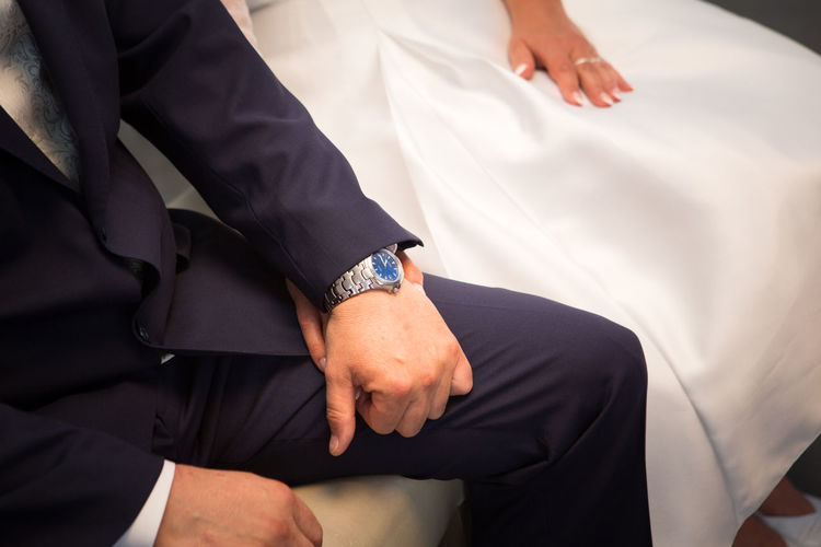 Midsection of newlywed couple holding hands sitting in wedding ceremony
