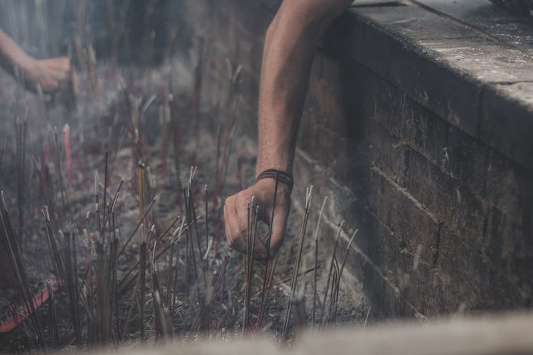 Cropped hand of man placing lit incense stick in ash