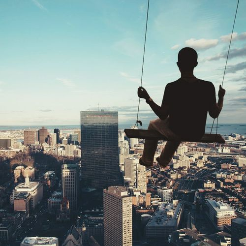 Rear view of man on swing against cityscape