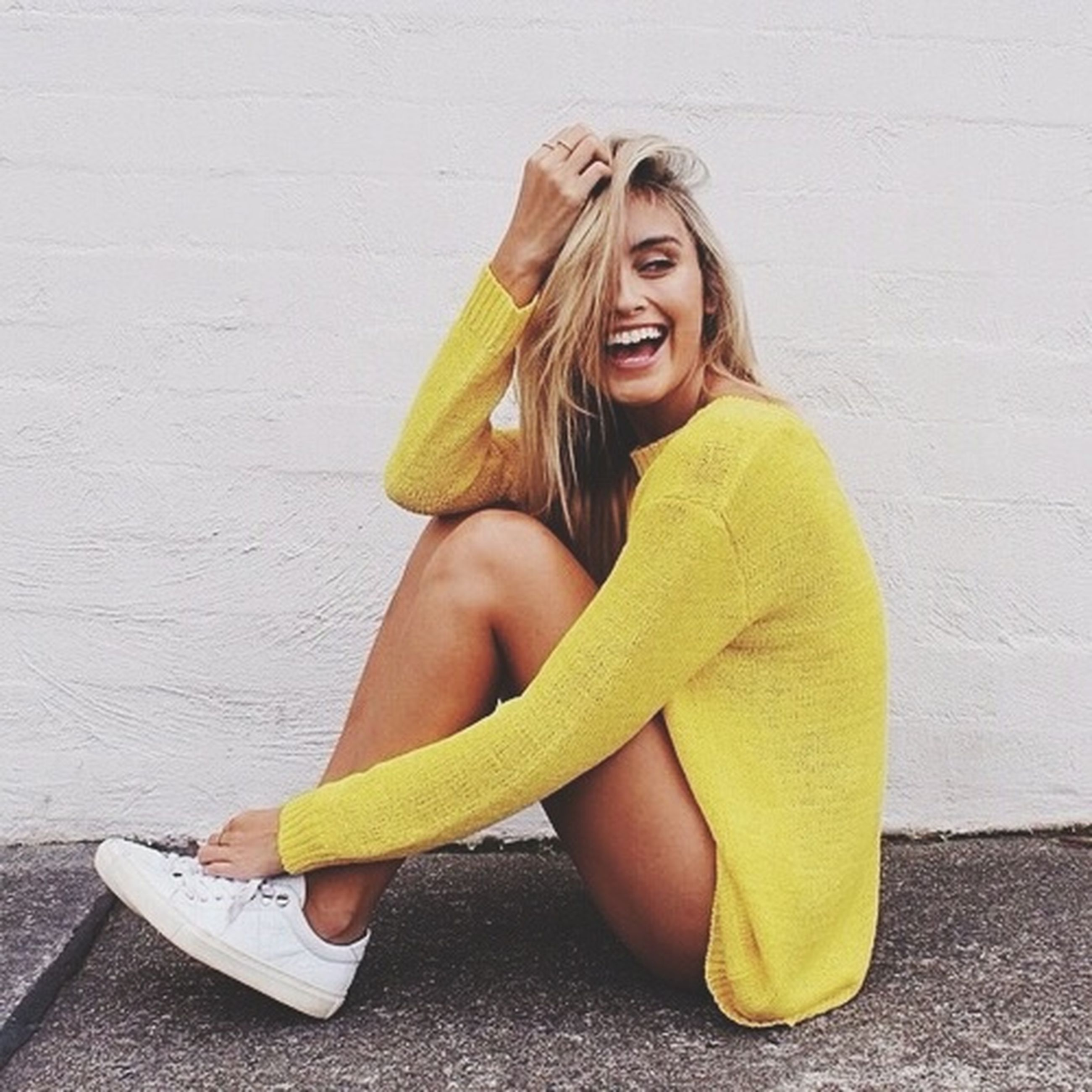 young adult, person, young women, front view, casual clothing, lifestyles, portrait, looking at camera, yellow, long hair, leisure activity, fashion, smiling, standing, holding, wall - building feature, dress