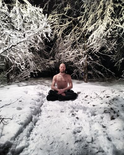 Full length of shirtless man sitting on snow covered land