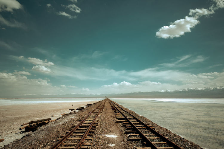 Railway tracks in the forlorn desert China View Cloud - Sky Desert Lake Landscape Mountain No People Outdoors Path Railway Track Saline Lake Sand Scenics Train Tracks Travel Destinations Way