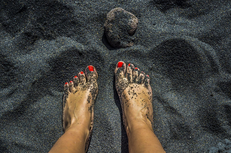 Low section of woman with red nail polish standing on black sand