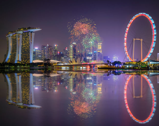 Firework Display By Lake And Marina Bay Sands In City At Night