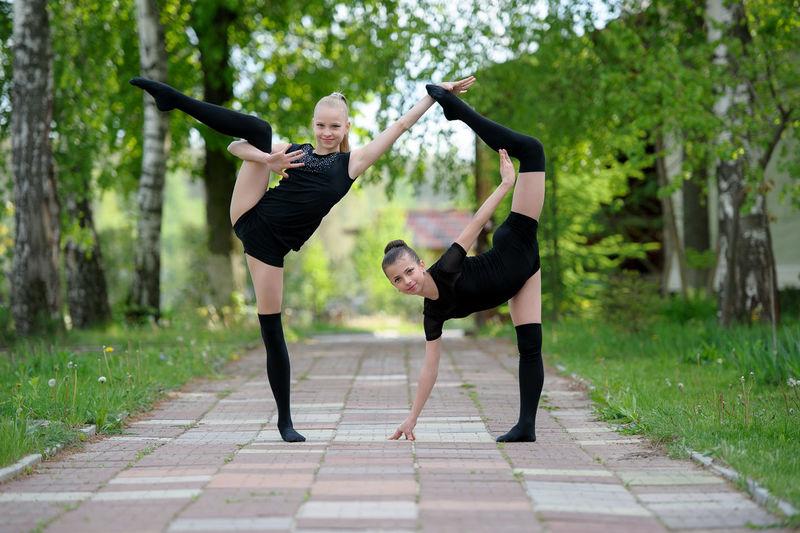 Portrait Of Girls Practicing Rhythmic Gymnastics On Footpath In Park