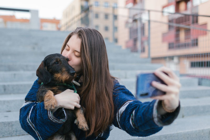 Woman photographing with dog