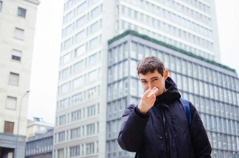 Portrait of young man gesturing against buildings in city