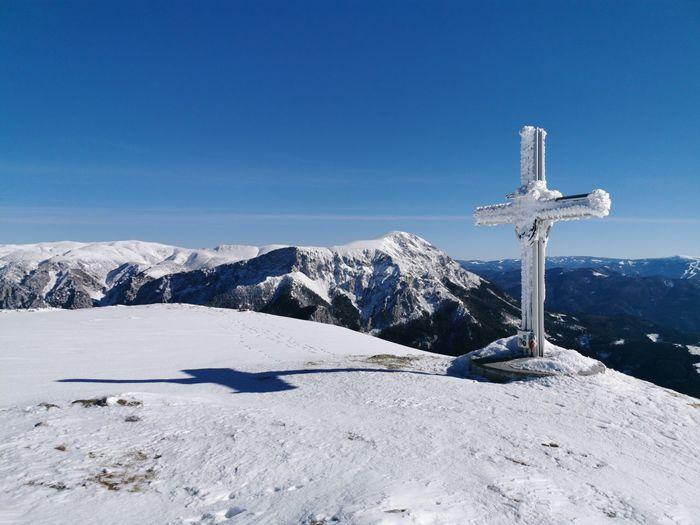 Cross on snowcapped mountain against blue sky