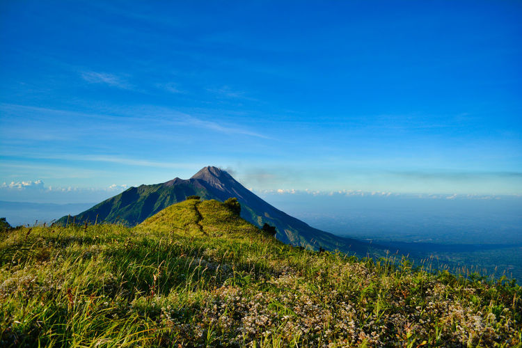 Very Beauty view Mt. Merapi. at Mt. Merbabu . Boyolali, Jawa Tengah, Indonesia. Volcanic Crater Mountain Peak Outdoors Volcano Mountain Range Day Travel Destinations Non-urban Scene Plant Grass Nature Land Tranquility Tranquil Scene Blue No People Beauty In Nature Cloud - Sky Landscape Environment Mountain Sky Scenics - Nature Green Color Idyllic