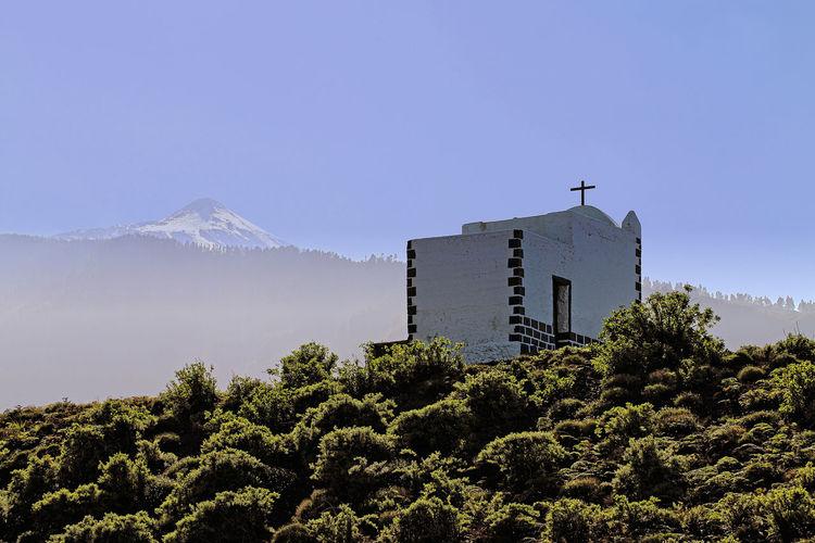 Christian chapel against clear blue sky