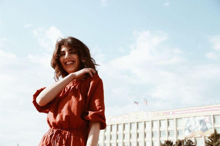 Portrait of smiling girl standing against sky