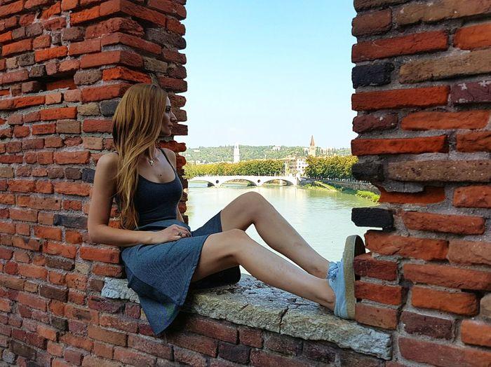 Woman sitting against brick wall